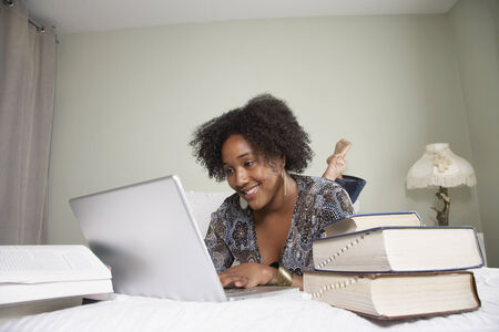 African woman studying on bed Stock Photo