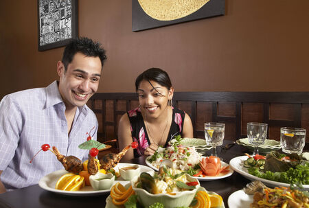 Multi-ethnic couple with table full of food Stock Photo