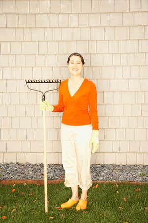 girl in full growth: Asian woman holding rake LANG_EVOIMAGES