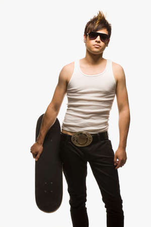 vietnamese ethnicity: Hispanic man holding skateboard LANG_EVOIMAGES