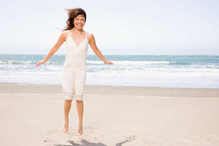 pacific islander ethnicity: Asian woman jumping on beach LANG_EVOIMAGES