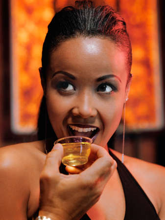 bestowing: African woman drinking shot at nightclub