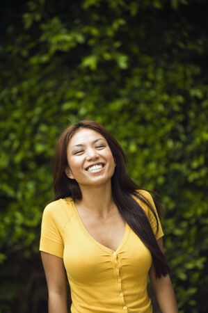 attired: Asian woman laughing outdoors