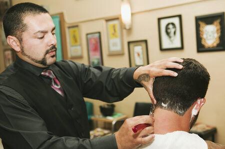 attired: Hispanic barber shaving man's neck