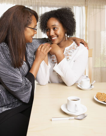 arm holding: African American mother and daughter smiling at each other