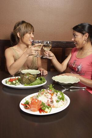 attired: Multi-ethnic women toasting at restaurant