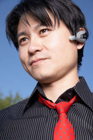 Asian man using hands free device Stock Photo