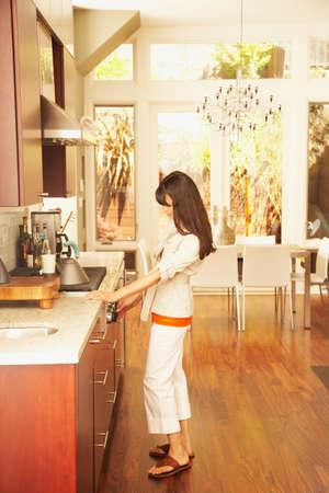 casualness: Hispanic woman turning on stove burner LANG_EVOIMAGES