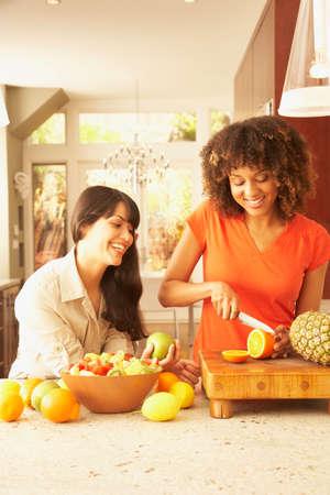 telecommuter: Multi-ethnic female friends cutting fruit