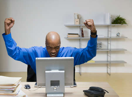 aggravated: African American businessman cheering at desk