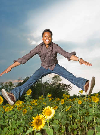 lighthearted: African man jumping in flower patch