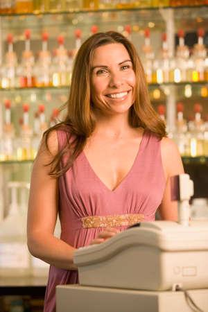 acknowledging: Hispanic cashier behind cash register