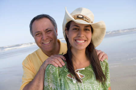 lighthearted: Hispanic father with hands on daughter's shoulders