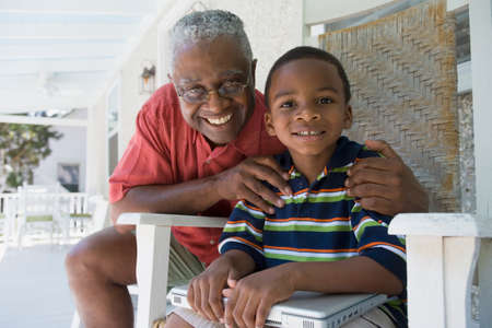 generation gap: African American grandfather hugging grandson