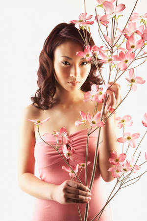 considerate: Asian woman holding branch with flowers