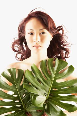 attentiveness: Nude Asian woman covered by large leaves LANG_EVOIMAGES