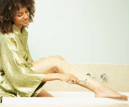 solicitous: African American woman shaving legs LANG_EVOIMAGES