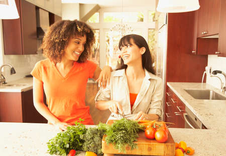 easygoing: Multi-ethnic female friends chopping vegetables