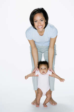 mother helping baby: African American mother helping baby stand LANG_EVOIMAGES