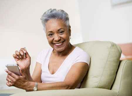 mujeres sentadas: Mujer mayor del afroamericano que sostiene organizador electrónico LANG_EVOIMAGES
