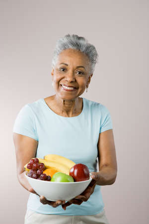 african american woman silhouette: Senior African American woman holding fruit bowl LANG_EVOIMAGES