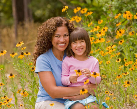 conferring: Hispanic mother and daughter in flower patch LANG_EVOIMAGES