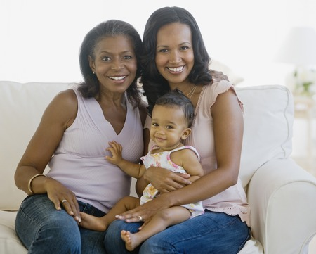 African American grandmother, mother and baby on sofa LANG_EVOIMAGES