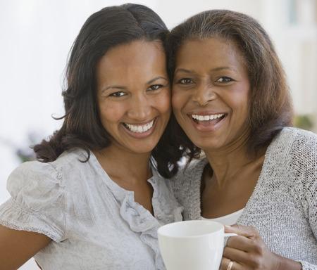 mujeres sentadas: Madre afroamericana y abrazos hija adulta