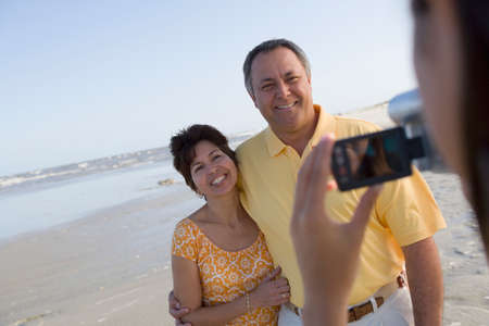 recorded: Hispanic couple being video recorded at beach