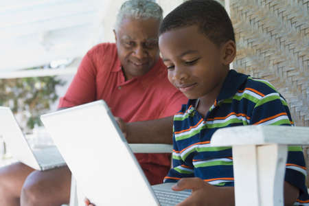 generation gap: African American grandfather and grandson looking at laptop LANG_EVOIMAGES