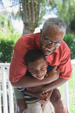 rebelling: African American grandfather hugging grandson