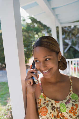 mischeif: African woman talking on telephone LANG_EVOIMAGES