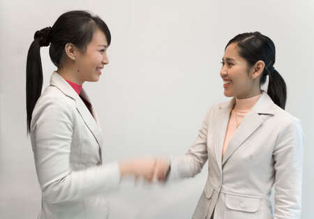 jointly: Asian businesswomen shaking hands