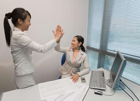 motioning: Asian businesswomen high-fiving