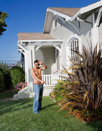 barechested: Bare-chested Hispanic man watering plants
