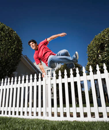 salto de valla: Hombre de salto hispana sobre la cerca LANG_EVOIMAGES