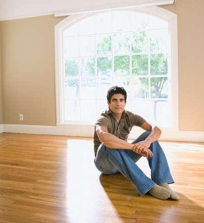 fleeing: Hispanic man sitting in new house LANG_EVOIMAGES