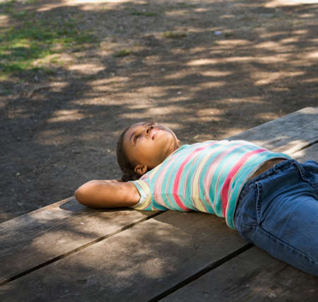 African American girl laying on picnic table