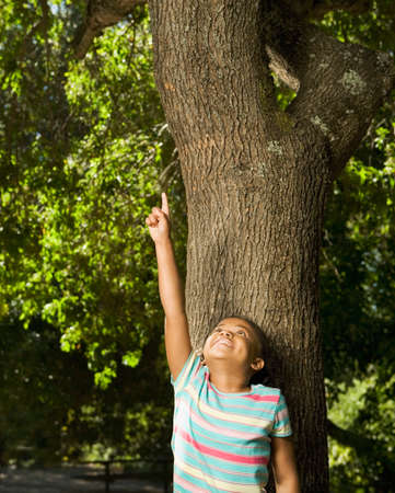 spectating: African American girl pointing at tree