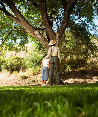 jesting: African American girl and Park Ranger looking at tree