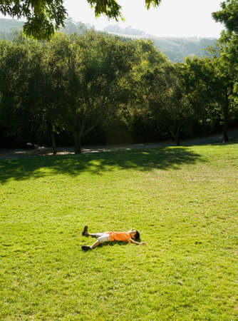 Asian boy laying in grass Stock Photo