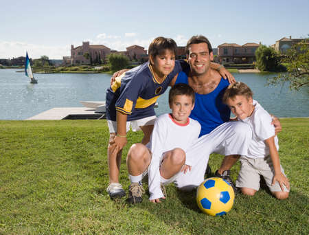 impersonal: Hispanic father and sons with soccer ball