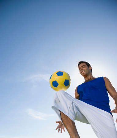 easygoing: Hispanic man bouncing soccer ball on knee LANG_EVOIMAGES