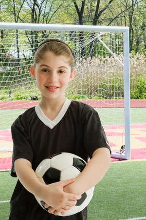 irish ethnicity: Mixed Race girl holding soccer ball LANG_EVOIMAGES