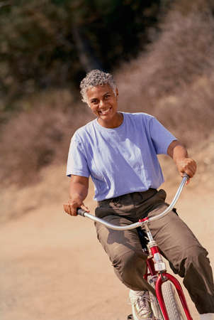 seventy two: Senior African American woman riding bicycle