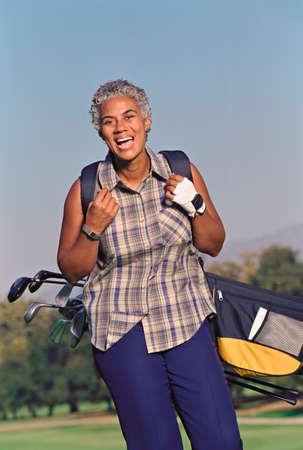 ceasing: Senior African American woman carrying golf bag LANG_EVOIMAGES