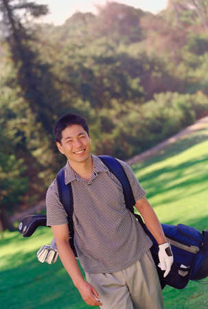seventy two: Asian man carrying golf bag
