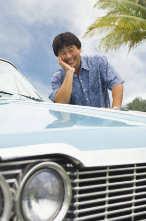 prevailing: Asian man leaning on car