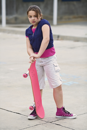 tomboy: Mixed Race girl holding skateboard