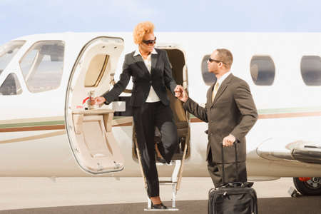 ostentatious: African American businesswoman getting off airplane